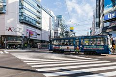 Commercial modern building with moving vintage bus on crosswalk on the road in Sapporo in Hokkaido, Japan.  stock photo