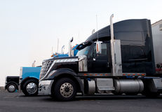 Commercial modern and classic semi trucks in truck stop line Stock Photography