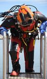 Commercial offshore diver with anti contamination suit and helmet. Commercial diver with a helmet ready to dive in the oil and gas industry, wearing an anti Royalty Free Stock Photography