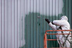 Commercial Painter. A commercial painter on an industrial lift spray painting a steel exterior wall or duct Stock Images