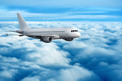Commercial passenger airplane flying over clouds. Large commercial passenger jet on its way to destination high above the clouds Stock Photos
