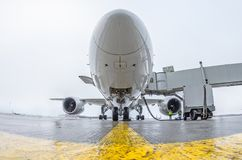 Commercial passenger airplane in the parking at the airport with a nose forward and a gangway - front view. Royalty Free Stock Photography