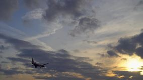 Commercial passenger plane flies toward sunset. UltraHD stock footage. Commercial passenger plane flies toward sunset. Orange and purple clouds, blue sky in the stock footage