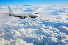 Commercial passenger plane flying above clouds Stock Photo