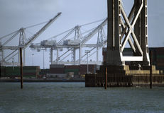 Commercial Port. The cranes of a modern container terminal viewed between the supports of a large road bridge stock photography