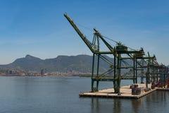 Commercial Port Cranes of Rio de Janeiro. Rio de Janeiro, Brazil - January 18, 2018: Port cranes along the Rio-Niteroi bridge. Skyline and mountains of the city Stock Photography
