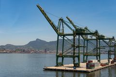 Commercial Port Cranes of Rio de Janeiro. Rio de Janeiro, Brazil - January 18, 2018: Port cranes along the Rio-Niteroi bridge. Skyline and mountains of the city Stock Image
