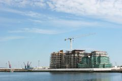 Commercial Property Boom. New commercial properties, overlooking water, under building construction and cloaked in scaffolding with a large crane in view and a Royalty Free Stock Photography