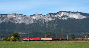 Commercial red train travels to the Austrian Alps. Royalty Free Stock Photos