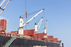 Commercial ship with cranes while unloading container to the shi Royalty Free Stock Image