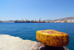 Commercial shipping. Rusty yellow anchor with big commercial and service ships in the background Stock Photography