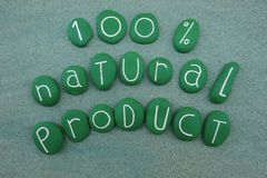 100 percent natural product, slogan with green painted stones over green sand. Commercial slogan with green painted composition over green sand about natural Stock Image