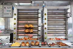 Commercial Stainless Steel Rotisserie Oven. A commercial grade large stainless steel rotisserie oven cooking chicken, ham, skewers, and vegetables Royalty Free Stock Photography