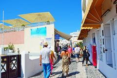 Commercial street Fira Santorini Greece. Tourists walking on the main commercial street lined up with cozy shops in Fira .The town of Fira is a typical Cycladic Stock Photos