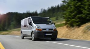 Commercial van drive by mountain road royalty free stock photo