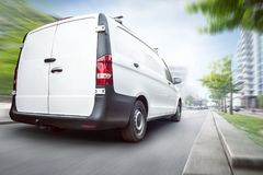 Commercial van driving in the city. Rear view of a white commercial van driving in a city. Motion blurred city background with buildings and trees stock photography