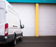 Commercial van for transporting cargo waiting by the warehouse g. Modern compact van for the delivery of commercial goods and local cargo transportation, as well Stock Photo