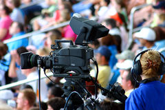 Commercial videographer. With camera in clear focus and audience blurred Stock Image