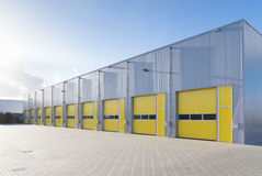 Commercial warehouse. Exterior of a commercial warehouse with yellow roller doors Stock Photos