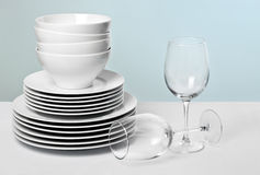 Commercial White Dishes and Crystal Wine Glasses. White plates and bowls with wine glasses against pastel blue background Stock Image