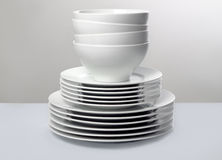 Commercial white dishes on neutral background. Stack of shiny white plates and bowls against simple monochromatic background Stock Photography