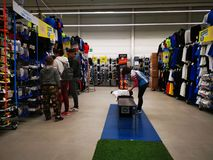 Commercial worker arranging the products and customers at Decathlon. Romania.  Decathlon is a manufacturer and distributor of sporting goods, sports equipment royalty free stock image