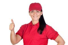 Commerciante del Brunette con l'uniforme rossa che dice BENE Immagine Stock