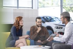 Commerciante di automobile che mostra un'offerta ai suoi clienti felici in uno showro dell'automobile immagini stock
