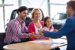 Commerciante di automobile che vende nuova automobile alla giovane famiglia con il bambino Fotografia Stock Libera da Diritti
