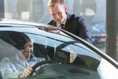 Commerciante di automobile con il cliente fotografia stock