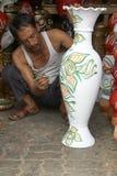 Commerciante di verniciatura del vaso alla sua piccola cabina fotografia stock