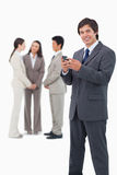 Commerciante sorridente con il cellulare ed i colleghi Fotografia Stock