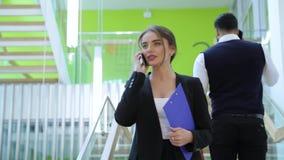 Commercieel centrum Vrouw die op telefoon in de bureaubouw spreken stock video