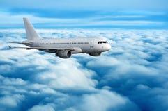 Commercieel passagiersvliegtuig dat over wolken vliegt Stock Foto's