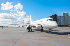 Commercieel passagiersvliegtuig in het parkeren bij de luchthaven met een voorwaartse neus en een doorgang Stock Afbeelding