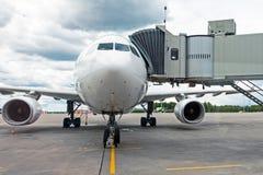 Commercieel passagiersvliegtuig in het parkeren bij de luchthaven met een voorwaartse neus en een doorgang - vooraanzicht Stock Foto's