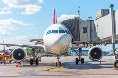 Commercieel passagiersvliegtuig in het parkeren bij de luchthaven met een voorwaartse neus en een doorgang - vooraanzicht De dien Stock Foto