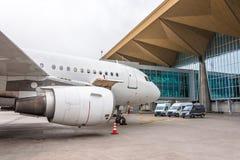 Commercieel passagiersvliegtuig in het parkeren bij de luchthaventerminal met een voorwaartse neus en een doorgang - vooraanzicht Stock Foto's