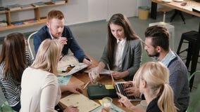 Commercieel team bij de lijst samenkomende diverse mensen die aan creatieve duurzame ideeën in modern startbureau deelnemen stock footage