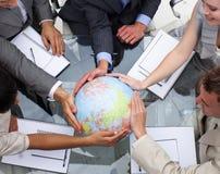 Commercieel team dat een aardse bol houdt royalty-vrije stock foto