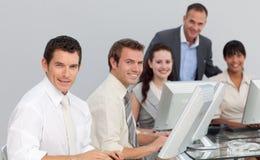 Commercieel team dat met computers in een bureau werkt Stock Afbeelding