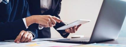 Commercieel team dat tablet en laptop computer met behulp van om in het bureau te werken aandeel van de banner voor advertenties stock fotografie