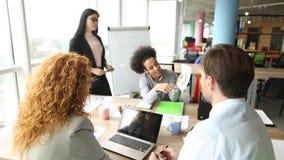 Commercieel team die aan diagram in modern bureau werken stock videobeelden