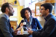 Commercieel team die in cafetaria en het drinken espresso werken Stock Foto's