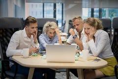 Commercieel team die computer met geschokte uitdrukkingen bekijken royalty-vrije stock foto's