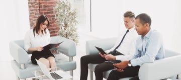 Commercieel team die discussienota's bestuderen, die in het bureau zitten stock foto's