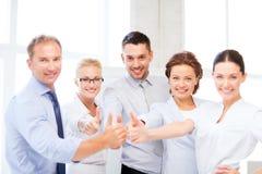 Commercieel team die duimen in bureau tonen Stock Afbeelding