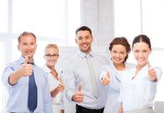 Commercieel team die duimen in bureau tonen Royalty-vrije Stock Afbeeldingen