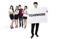 Commercieel team die een raad met groepswerktekst houden Stock Afbeelding