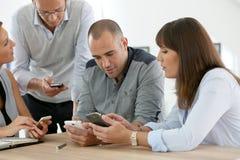 Commercieel team die elektronische apparaten met behulp van Royalty-vrije Stock Afbeelding